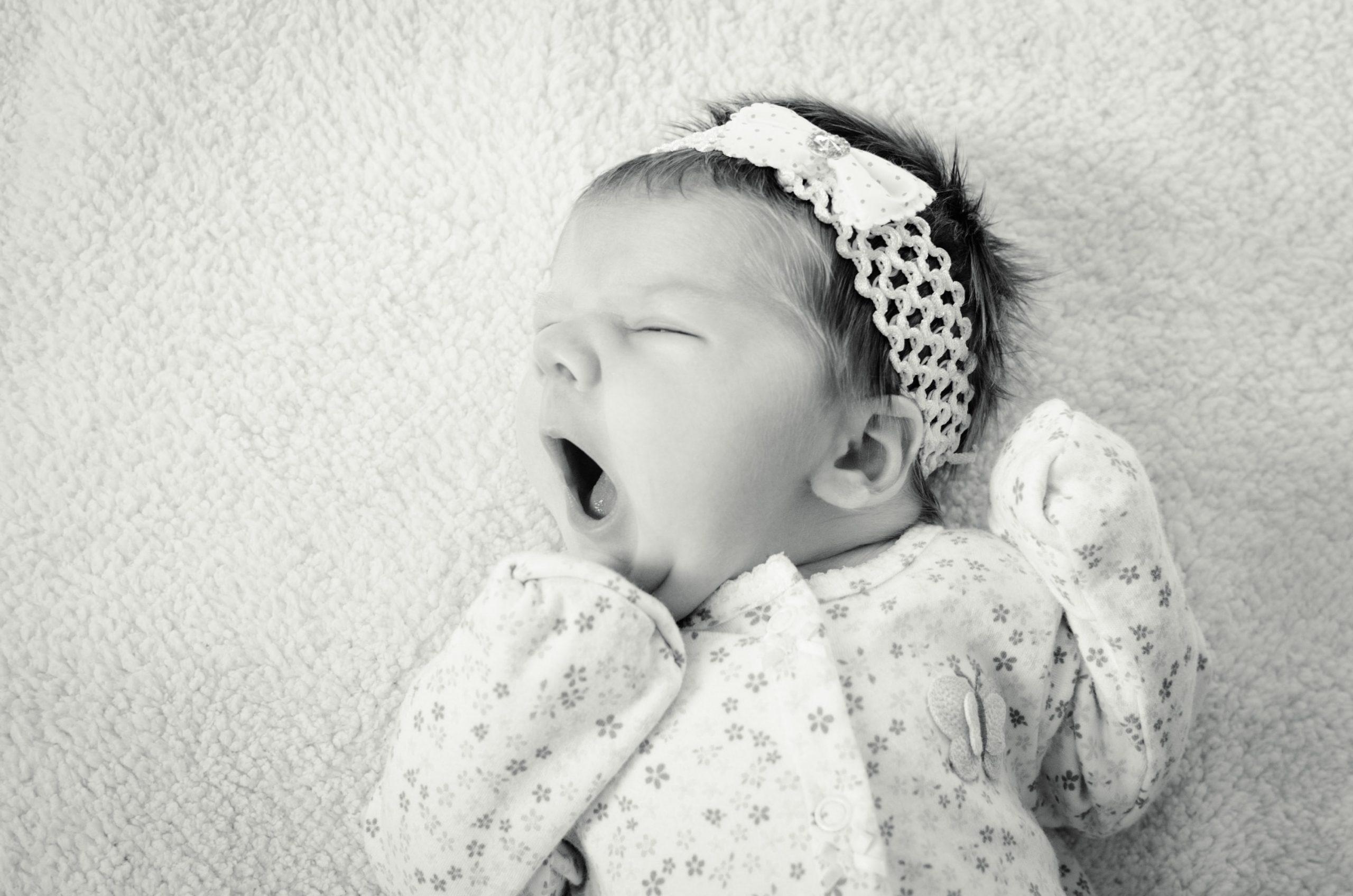 Photo of yawning baby girl laying on blanket
