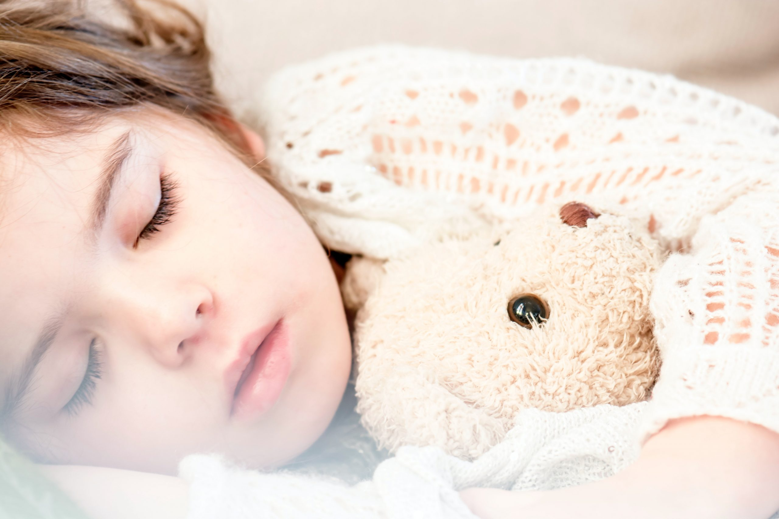 Photo of sleeping child snuggles with teddy